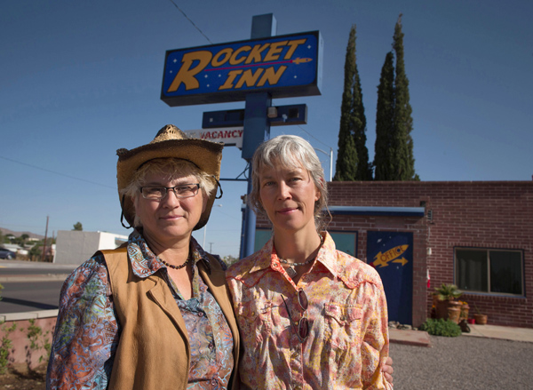Val Wilkes, 54, and her wife Cydney Wilkes, 56, stand outside their motel, the Rocket Inn, in Truth or Consequences