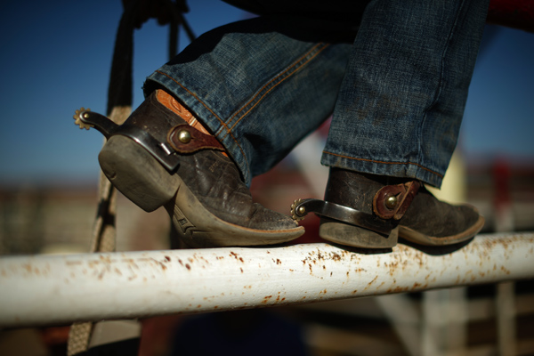 A boy wears spurs on his cowboy boots at the rodeo in Truth or Consequences