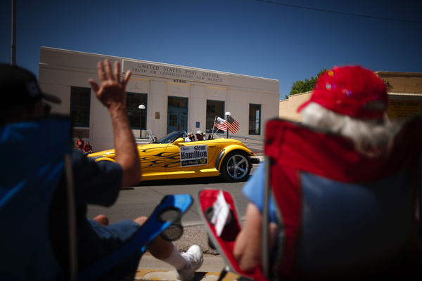 People wave at a car in the annual Fiesta parade in Truth or Consequences