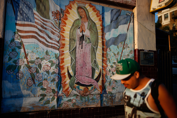 A man walks past a mural showing the Mexican, Salvadoran, Guatemalan and United States flags surrounding the Virgin of Guadalupe, patroness of Latin America, in the Westlake area of Los Angeles, home to many Mexican and Central American immigrants