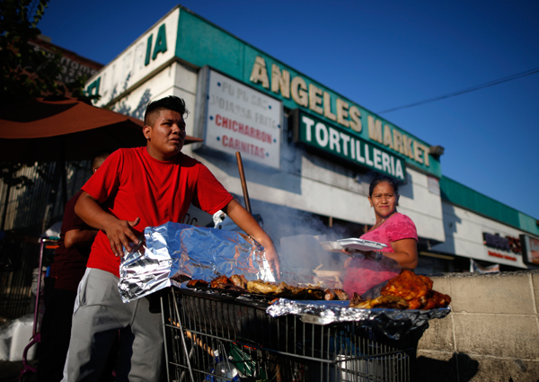 A man cooks meat in a shopping cart in the Westlake area of Los Angeles, home to many Mexican and Central American immigrants
