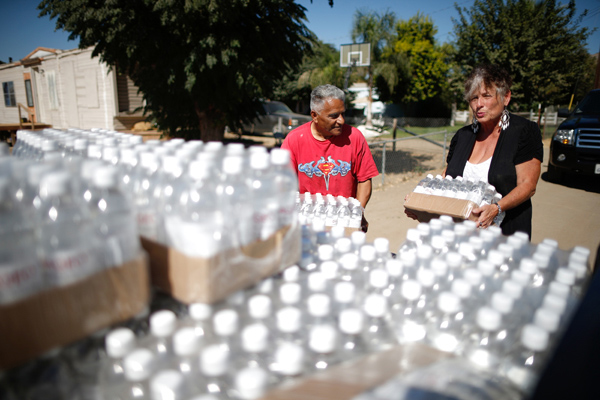 Donna Johnson, 70, lifts pallets of donated bottled water from the back of her truck during her daily delivery run to residents whose wells have run dry in Porterville