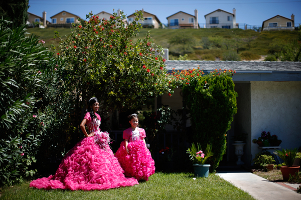Mimi Pineda, 15, whose parents are from El Salvador, stands outside her aunt's house before her quinceanera with Maybelin Ramirez, 6, in Santa Clarita