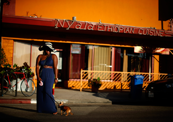 A woman poses for a friend's photo in the Little Ethiopia area of Los Angeles