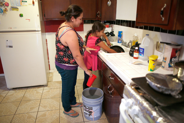 Marisela Corona, 26, whose well has run dry, washes dishes with her daughter Andrea Andrade Corona, 8, from a water bucket in Porterville