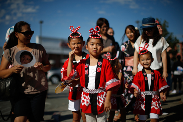 Sena Nagata, 7, Lana Osumi, 8, and Seri Nagata, 4, wave as they watch a parade in the Little Tokyo area of Los Angeles