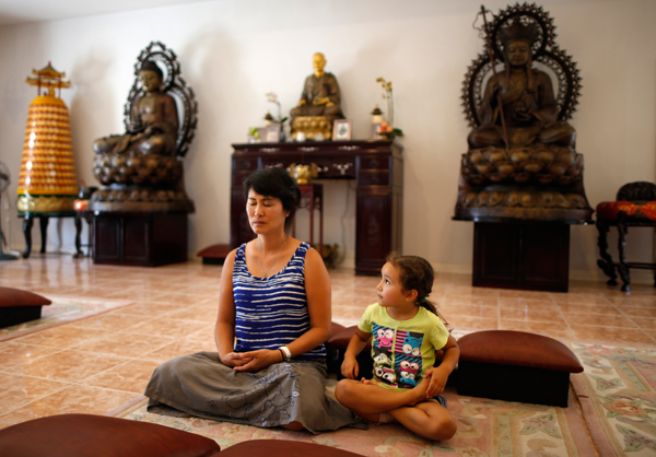 Sarah Kim, who emigrated from South Korea, meditates with Sabina Mayorga, 4, whose parents are from Mexico, at Lu Mountain Buddhist Temple in Rosemead