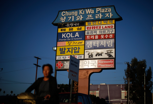 A woman cycles past a strip mall sign in the Koreatown area of Los Angeles
