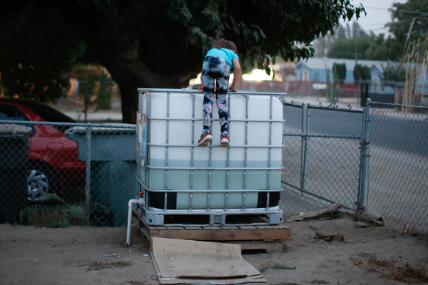 Abigail Beltran, 6, whose family's well has run dry, climbs on a water storage tank in her front yard in Porterville