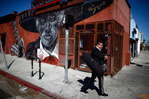 A mariachi musician walks past a mural depicting a mariachi in the Boyle Heights area of Los Angeles