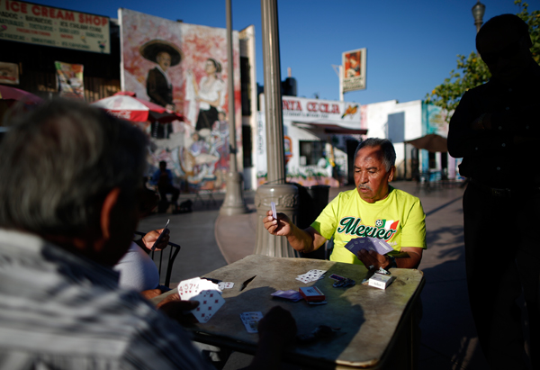 Men play cards in Mariachi Plaza in the Boyle Heights area of Los Angeles