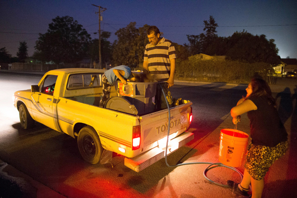 Macario Beltran, 41, a mechanic whose family's well has run dry, fills containers in his truck with water from the fire station, with his daughters Abigail, 6, and Denika, 10, in Porterville