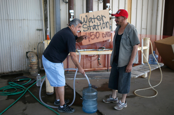 Pastor Frankie Olmedo, 56, who volunteers four hours a day to hand out water, fills up a container for Luis Bocanegra, 35, in Porterville