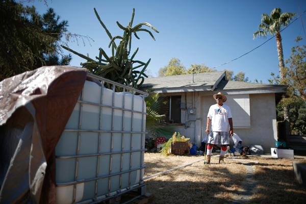 Manuel Rodriguez, 83, watches as workmen install a water pump to carry water from an outdoor container into his home in Porterville