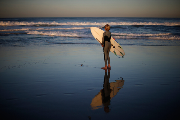 Carlos Price Gracida, 13, looks at the ocean after finishing surfing at sunrise in Hermosa Beach, California March 24, 2015. The group of friends surf at sunrise most mornings, then shower outside and walk to school. Picture taken March 24, 2015. REUTERS/Lucy Nicholson
