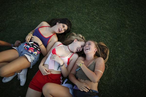 Women lie on the grass to listen to Hozier at the Coachella Valley Music and Arts Festival in Indio, California April 11, 2015. REUTERS/Lucy Nicholson - RTR4WZ9H