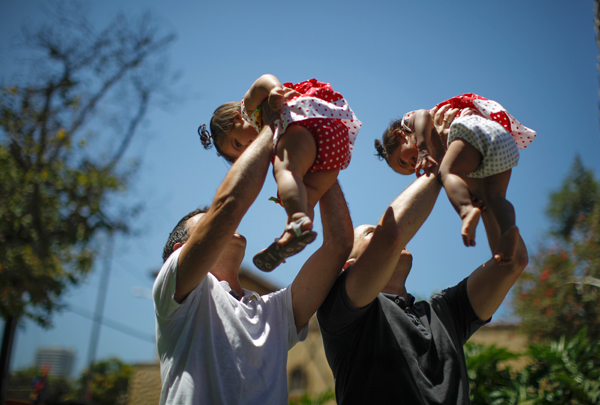In a file picture taken on June 26, 2013, Jason Howe, 48, and Adrian Perez (L), 48, who were married in Spain, and again in California, hold their one-year-old twin daughters Clara (R) and Olivia at a playground in West Hollywood, California after the United States Supreme court ruled on California's Proposition 8 and the federal Defense of Marriage Act, June 26, 2013. REUTERS/Lucy Nicholson