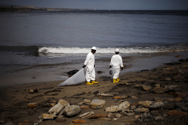 Workers clean up an oil slick along the coast of Refugio State Beach in Goleta, California, United States, May 21, 2015. Up to 2,500 barrels (105,000 gallons) of petroleum, according to latest estimates, gushed onto San Refugio State Beach and into the Pacific about 20 miles (32 km) west of Santa Barbara on Tuesday when an underground pipeline that runs along the coastal highway inexplicably burst. REUTERS/Lucy Nicholson - RTX1E1IT