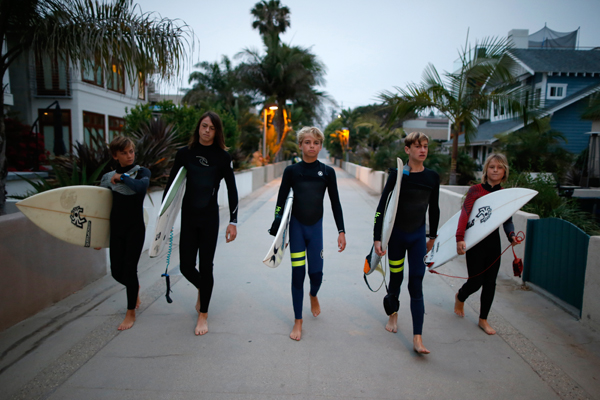 Kevin Elliott, 12, (L-R), Sebastian Rodriguez, 13, Kieran Walls, 13, Luke Personius, 12, and Shane Moseley, 13, walk to the beach to surf before school at sunrise in Hermosa Beach, California March 31, 2015. The group of friends surf at sunrise most mornings, then shower outside and walk to school. Picture taken March 31, 2015. REUTERS/Lucy Nicholson