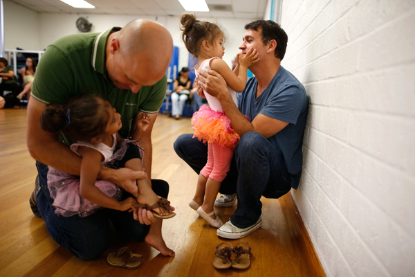 Jason Howe, 50, (L) and his husband Adrian Perez-Boluda, 50, help their twin three-year-old daughters Olivia (2nd R) and Clara put on their shoes after their ballet class in Los Angeles, California, United States, June 25, 2015. Howe and Perez-Boluda got married in Spain and in California in 2008. REUTERS/Lucy Nicholson