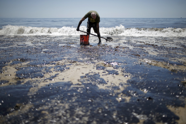 William McConnaughey, 56, who drove from San Diego to help shovel oil off the beach, stands in an oil slick in bare feet along the coast of Refugio State Beach in Goleta, California, United States, May 20, 2015. A pipeline ruptured along the scenic California coastline on Tuesday, spilling some 21,000 gallons (79,000 liters) of oil into the ocean and on beaches before it could be secured, a U.S. Coast Guard spokeswoman said. REUTERS/Lucy Nicholson - RTX1DV3J