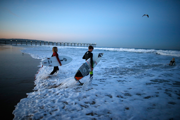 Luke Personius, 12, (R) and Shane Moseley, 13, go surfing before school at sunrise in Hermosa Beach, California March 24, 2015. The group of friends surf at sunrise most mornings, then shower outside and walk to school. Picture taken March 24, 2015. REUTERS/Lucy Nicholson