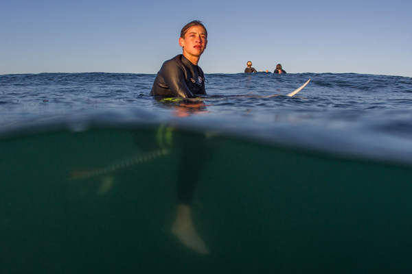 Luke Personius, 12, waits for a wave as he surfs before school at sunrise in Hermosa Beach, California April 2, 2015. The group of friends surf at sunrise most mornings, then shower outside and walk to school. Picture taken April 2, 2015. REUTERS/Lucy Nicholson