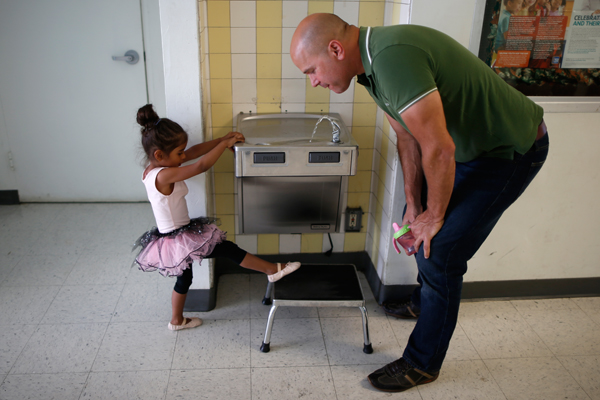 Jason Howe, 50, (R) drinks at a water fountain with his three-year-old daughter Clara after her ballet class in Los Angeles, California, United States, June 25, 2015. Howe, 50, and his husband Adrian Perez-Boluda, 50, got married in Spain and in California in 2008. REUTERS/Lucy Nicholson