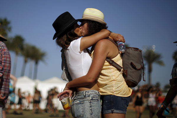 A couple kisses as they wait in line for food at the Coachella Valley Music and Arts Festival in Indio, California April 11, 2015. REUTERS/Lucy Nicholson - RTR4WZ81