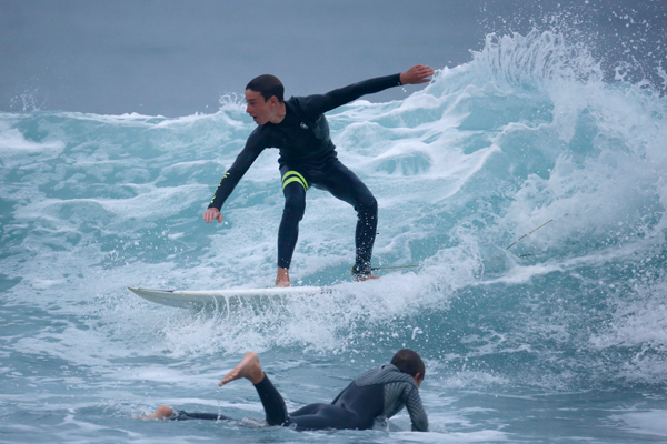 Luke Personius, 12, (top) surfs past Kevin Elliott, 12, before school at sunrise in Hermosa Beach, California March 31, 2015. The group of friends surf at sunrise most mornings, then shower outside and walk to school. Picture taken March 31, 2015. REUTERS/Lucy Nicholson