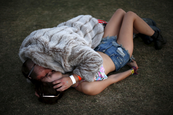 A couple lies on the grass before Kaskade plays at the Coachella Valley Music and Arts Festival in Indio, California April 12, 2015. REUTERS/Lucy Nicholson - RTR4X36E