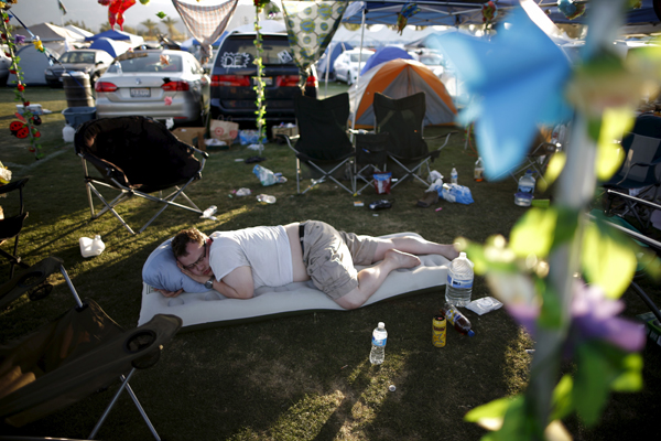 A man takes a nap in the car camping area at the Coachella Valley Music and Arts Festival in Indio, California April 11, 2015. REUTERS/Lucy Nicholson - RTR4WZ9L