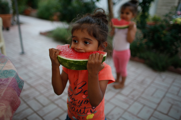 Twins Olivia (R) and Clara, 3, eat watermelon at their home in Los Angeles, California, United States, June 25, 2015. Their parents Jason Howe, 50, and Adrian Perez-Boluda, 50, got married in Spain and in California in 2008. REUTERS/Lucy Nicholson