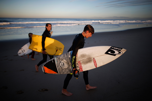 Luke Personius, 12, (R) walks up the beach after going surfing before school at sunrise in Hermosa Beach, California March 24, 2015. The group of friends surf at sunrise most mornings, then shower outside and walk to school. Picture taken March 24, 2015. REUTERS/Lucy Nicholson