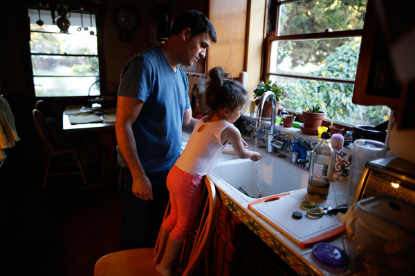 Adrian Perez-Boluda, 50, (L) helps his three-year-old daughter Olivia wash her hands before dinner in Los Angeles, California, United States, June 25, 2015. Perez-Boluda and his husband Jason Howe, 50, got married in Spain and in California in 2008. REUTERS/Lucy Nicholson
