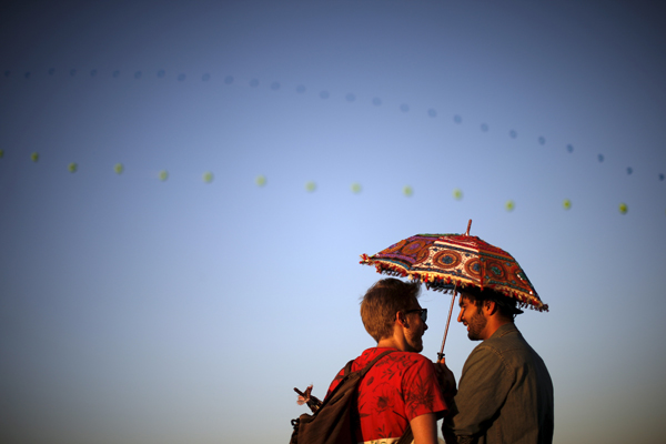 Two men share a parasol at the Coachella Valley Music and Arts Festival in Indio, California April 12, 2015. REUTERS/Lucy Nicholson - RTR4X3EU