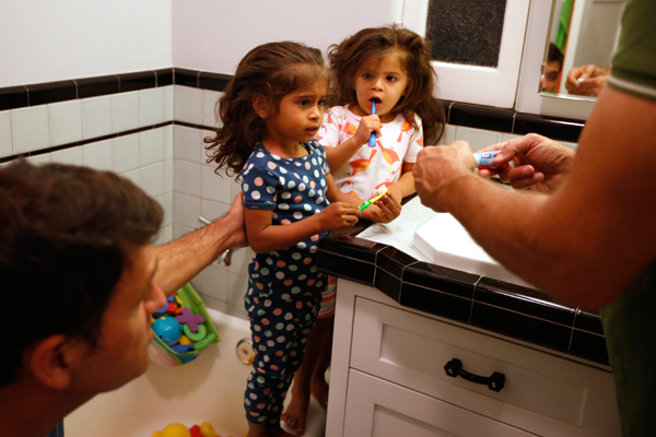 Jason Howe, 50, (R) and his husband Adrian Perez-Boluda, 50, help their twin three-year-old daughters Olivia (2nd R) and Clara brush their teeth before bed in Los Angeles, California, United States, June 25, 2015. Howe and Perez-Boluda got married in Spain and in California in 2008. REUTERS/Lucy Nicholson
