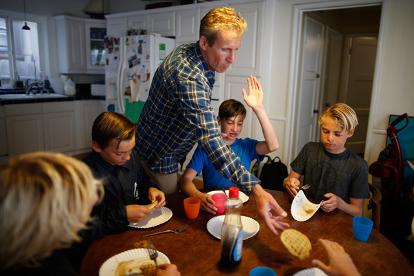 Matt Walls, 47, (3rd L) prepares waffles for his son and friends after they went surfing at sunrise before school (L-R) Carlos Price Gracida, 13, Kevin Elliott, 12, Luke Personius, 12, and Kieran Walls, 13, in Hermosa Beach, California March 31, 2015. The group of friends surf at sunrise most mornings, then shower outside and walk to school. Picture taken March 31, 2015. REUTERS/Lucy Nicholson
