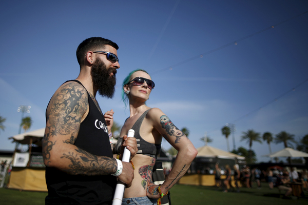 Dominic DeBonis, 31, (L) and Samantha Harris-Roberts, 41, from Somerset, England, walk through the Coachella Valley Music and Arts Festival in Indio, California April 10, 2015. REUTERS/Lucy Nicholson - RTR4WWA9