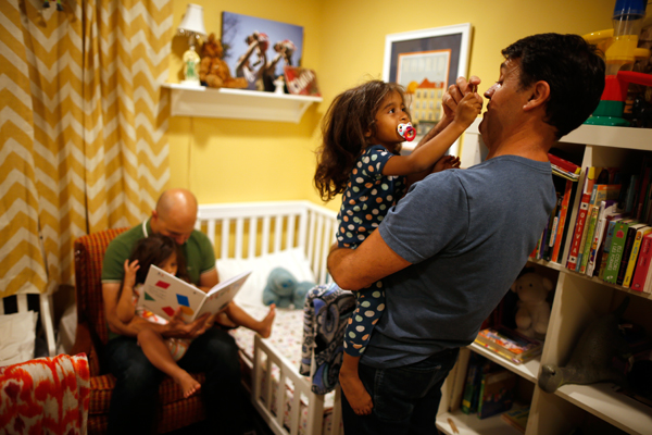 Jason Howe, 50, (2nd L) and his husband Adrian Perez-Boluda, 50, put their twin three-year-old daughters Olivia (L) and Clara to bed at their home in Los Angeles, California, United States, June 25, 2015. Howe and Perez-Boluda got married in Spain and in California in 2008. REUTERS/Lucy Nicholson