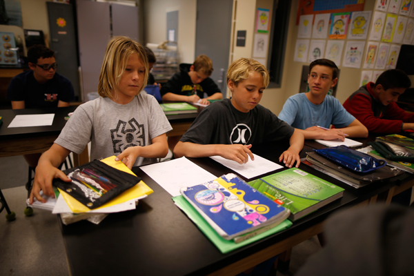 Shane Moseley, 13, (L-R), Kieran Walls, 13, and Luke Personius, 12, sit in class at Hermosa Valley School after surfing at sunrise in Hermosa Beach, California April 2, 2015. The group of friends surf at sunrise most mornings, then shower outside and walk to school. Picture taken April 2, 2015. REUTERS/Lucy Nicholson