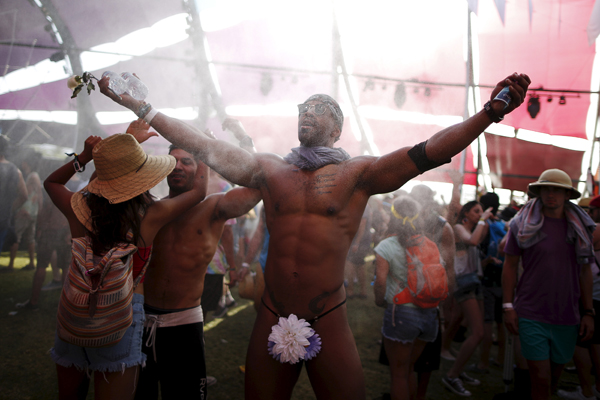 Cameron Pugh, 24, from Fresno, dances in the mist at the Coachella Valley Music and Arts Festival in Indio, California April 10, 2015. REUTERS/Lucy Nicholson - RTR4WVUL
