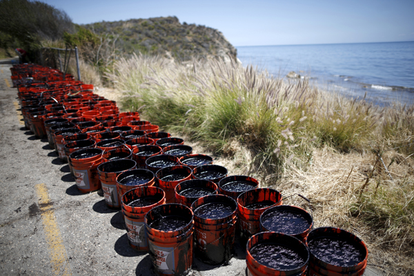Buckets of oil volunteers carried from an oil slick sit along the coast of Refugio State Beach in Goleta, California, United States, May 20, 2015. A pipeline ruptured along the scenic California coastline on Tuesday, spilling some 21,000 gallons (79,000 liters) of oil into the ocean and on beaches before it could be secured, a U.S. Coast Guard spokeswoman said. REUTERS/Lucy Nicholson - RTX1DV80