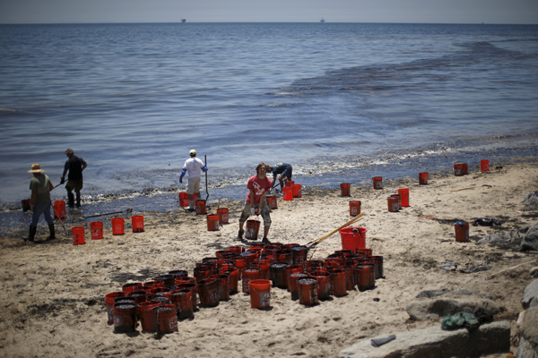 Volunteers fill buckets of oil from an oil slick along the coast of Refugio State Beach in Goleta, California, United States, May 20, 2015. A pipeline ruptured along the scenic California coastline on Tuesday, spilling some 21,000 gallons (79,000 liters) of oil into the ocean and on beaches before it could be secured, a U.S. Coast Guard spokeswoman said. REUTERS/Lucy Nicholson - RTX1DV4E