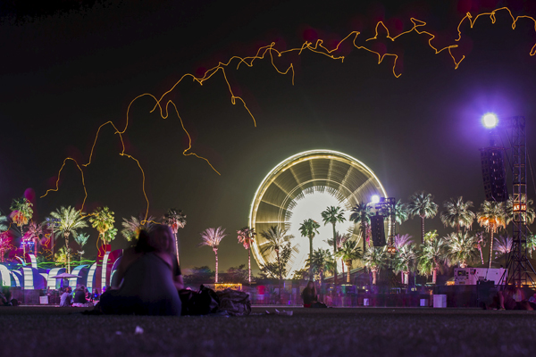 People sit under a row of lit balloons in front of a ferris wheel at the Coachella Valley Music and Arts Festival in Indio, California April 10, 2015. Picture taken with a long camera exposure. REUTERS/Lucy Nicholson - RTR4WW8B