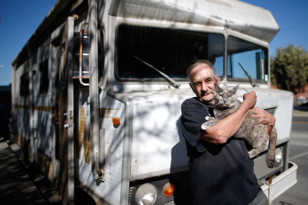 "Dan, 68, holds one of his three cats as he poses for a portrait by the RV in which he lives on the streets of Los Angeles, California, United States, November 12, 2015. Dan has been homeless for over a decade. He bought the RV from a couple who helped him out by selling it for $1. Los Angeles officials in September declared the rising problem of homelessness an ""emergency"" in the city and proposed spending $100 million to provide permanent housing and shelters to help the city's 26,000 indigent. The nation's second-largest city has nearly 18,000 individuals living on the streets, as opposed to shelters. REUTERS/Lucy Nicholson"