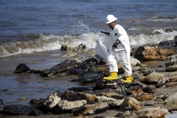 A worker climbs on rocks covered in oil as he cleans up an oil slick along the coast of Refugio State Beach in Goleta, California, United States, May 21, 2015. As much as 2,500 barrels (105,000 gallons) of crude oil, according to latest estimates, gushed onto San Refugio State Beach and into the Pacific west of Santa Barbara when an underground pipeline running parallel to a coastal highway there inexplicably burst on Tuesday morning. REUTERS/Lucy Nicholson - RTX1E1I2