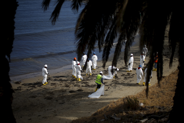 Workers clean up an oil slick along the coast of Refugio State Beach in Goleta, California, United States, May 21, 2015. Up to 2,500 barrels (105,000 gallons) of petroleum, according to latest estimates, gushed onto San Refugio State Beach and into the Pacific about 20 miles (32 km) west of Santa Barbara on Tuesday when an underground pipeline that runs along the coastal highway inexplicably burst. REUTERS/Lucy Nicholson - RTX1E1IR