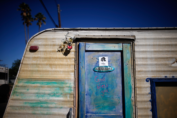 "A welcome sign is seen on the door of a caravan in a homeless RV and tent encampment near LAX airport in Los Angeles, California, United States, October 26, 2015. Los Angeles officials last month declared the rising problem of homelessness an ""emergency"" in the city and proposed spending $100 million to provide permanent housing and shelters to help the city's 26,000 indigent. The nation's second-largest city has nearly 18,000 individuals living on the streets, as opposed to shelters. REUTERS/Lucy Nicholson"
