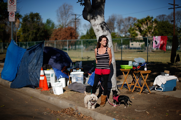 "Stacie McDonough, 51, poses for a portrait by her tent in a homeless RV and tent encampment near LAX airport in Los Angeles, California, United States, October 26, 2015. McDonough is an army veteran with a college degree who has been homeless for almost 2 weeks. Los Angeles officials last month declared the rising problem of homelessness an ""emergency"" in the city and proposed spending $100 million to provide permanent housing and shelters to help the city's 26,000 indigent. The nation's second-largest city has nearly 18,000 individuals living on the streets, as opposed to shelters. REUTERS/Lucy Nicholson"